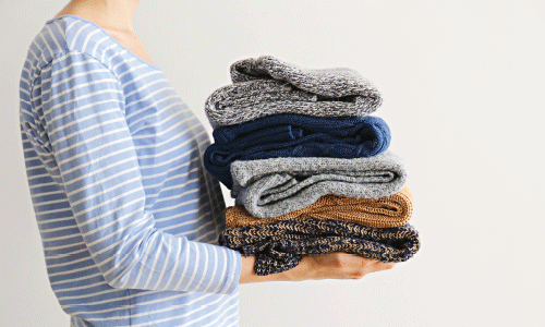 A woman carrying folded jumpers to put away.