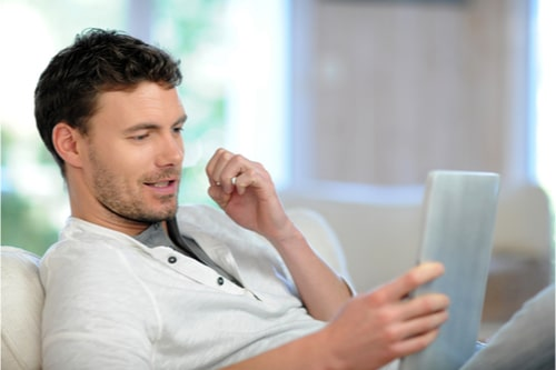 Man on sofa tracking parcel on tablet